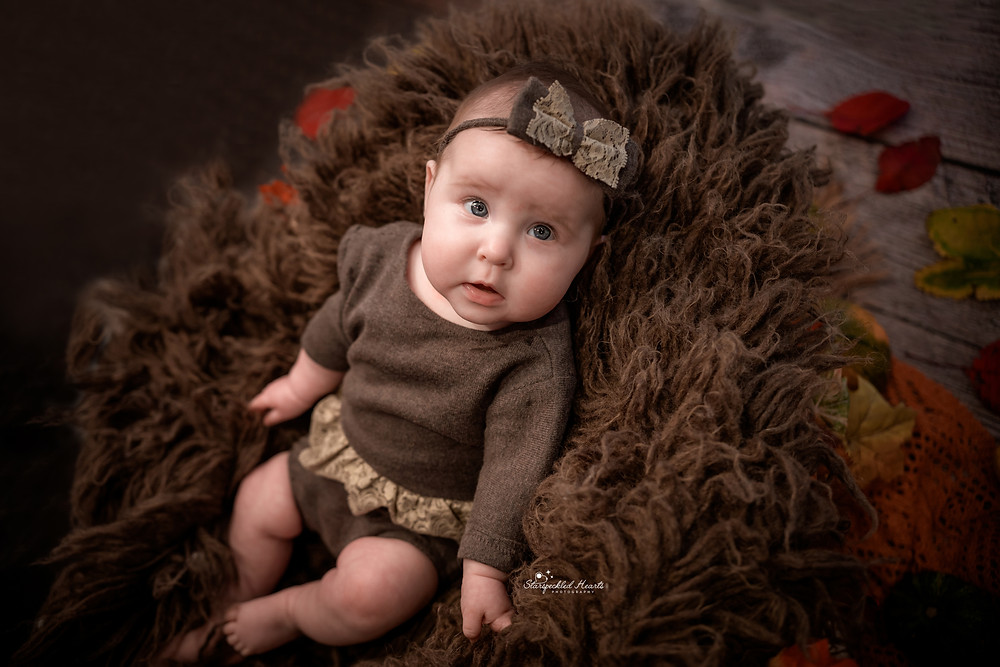 baby girl with blue eyes wearing a brown lacy romper and matching bow, lying in a brown fluffy rug surrounded by autumnal leaves