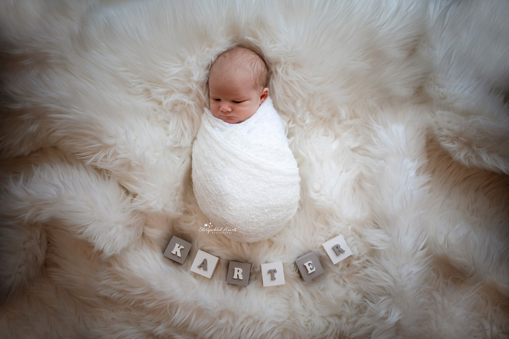 newborn baby wrapped in a white swaddle lying on a white furry rug with block letters below him, spelling out his name Karter