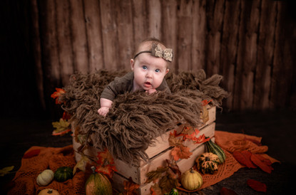 beautiful baby girl with blue eyes wearing a brown romper, lying in a crate surrounded by gourds and pumpkins on a dark wooden backdrop