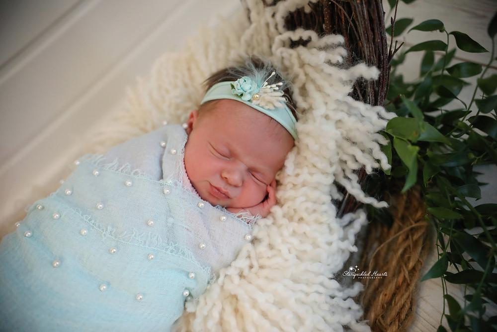 beautiful sleeping baby girl wearing a blue pearl embellished wrap