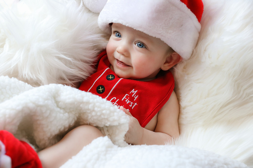 """smiling baby boy wearing santa hat and a red bib that says """"my first christmas"""""""