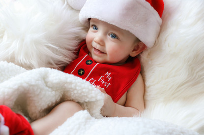 little boy wearing santa hat laying on white rug
