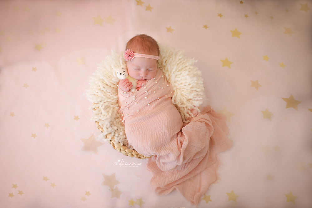 gorgeous sleeping baby girl wearing a pink textured wrap, laying in a white wicker basket, cuddling a white teddy