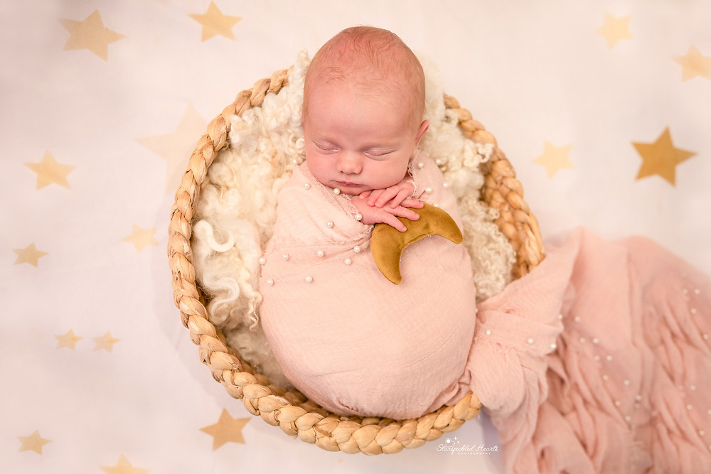 newborn wrapped in a pink pearl embellished wrap, holding on to a gold moon lying on a star backdrop