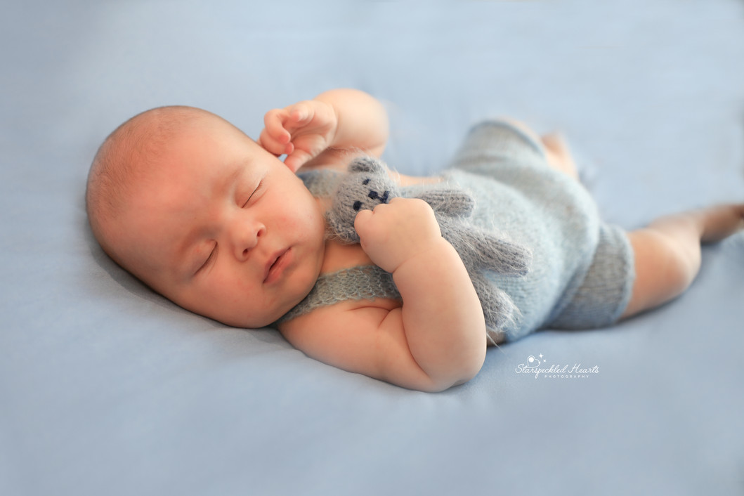 sweet sleeping newborn wearing blue, cuddling a blue teddy