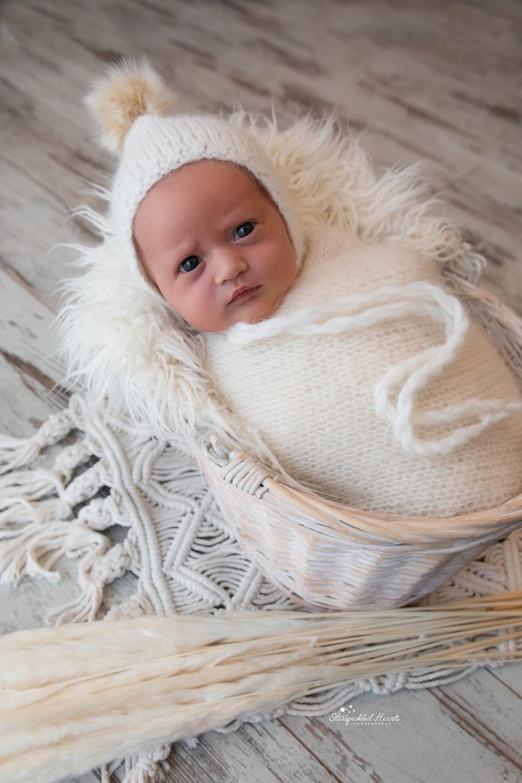 baby girl lying in a wicker basket with wide open eyes