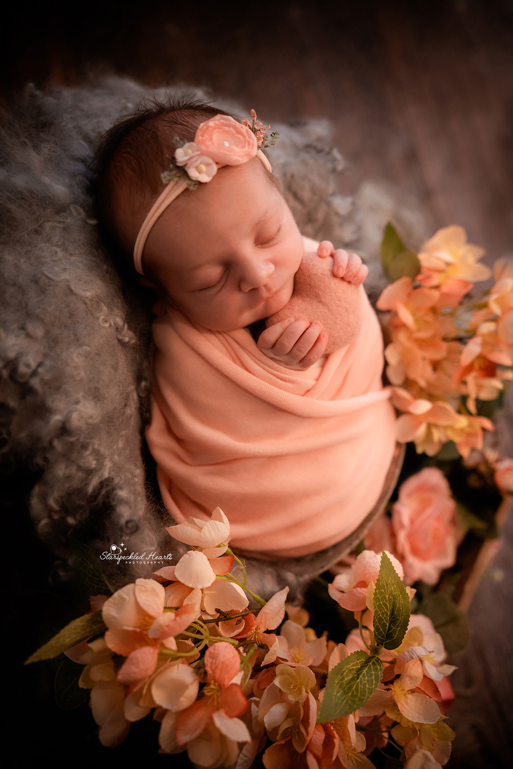 beautiful sleeping newborn baby girl wrapped in pink, holding a pink felt heart