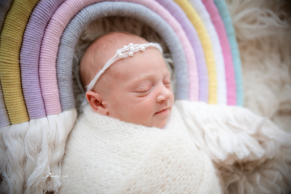 sleepy newborn girl wrapped in white, lying underneath a pastel macramé rainbow