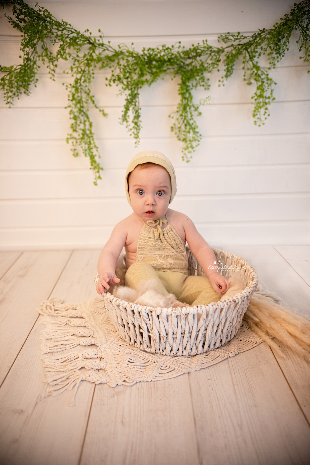 adorable baby girl wearing a lime green romper and bonnet set, sitting in a basket