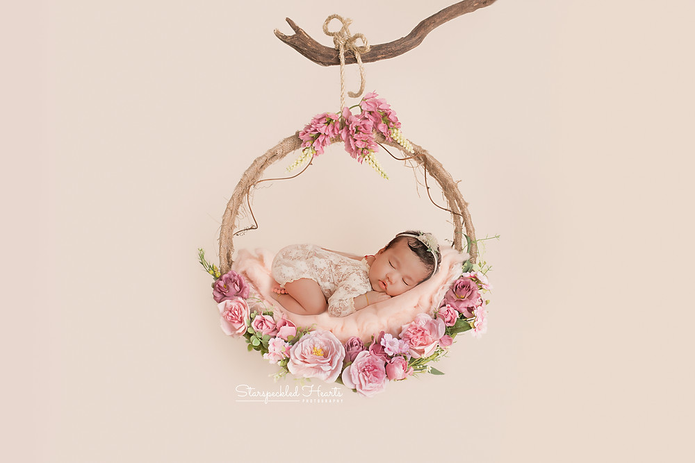 sleeping newborn baby girl laying on her tummy on a floral swing for her newborn photography session with starspeckled hearts photography in aldershot, hampshire