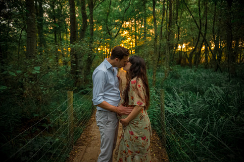 man and woman kissing standing in a forest with the sun setting behind them