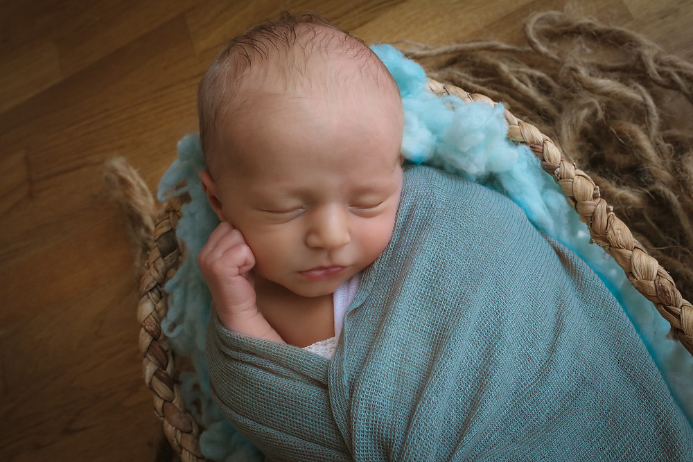sleepy newborn with hands up around his face, wearing duck egg blue wrap, lying in a brown basket with wicker trim