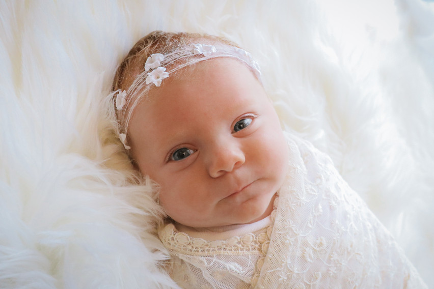 newborn girl wrapped in white wearing white floral headband
