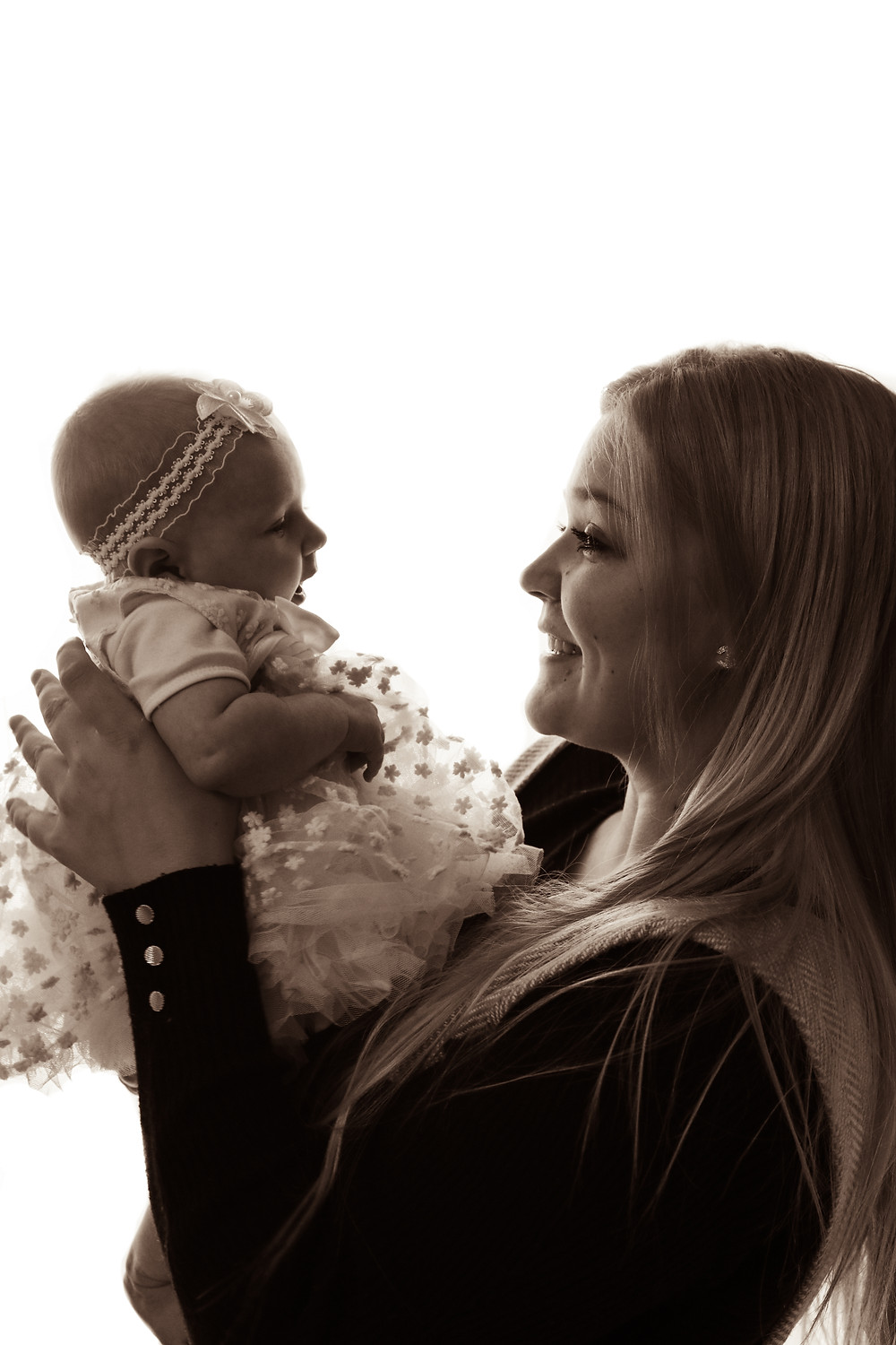 baby girl held up by smiling blonde woman