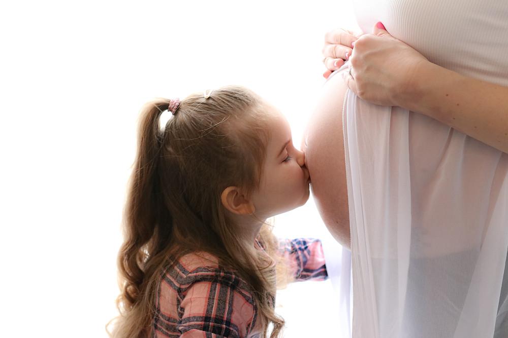 Child kissing pregnant mum's tummy.