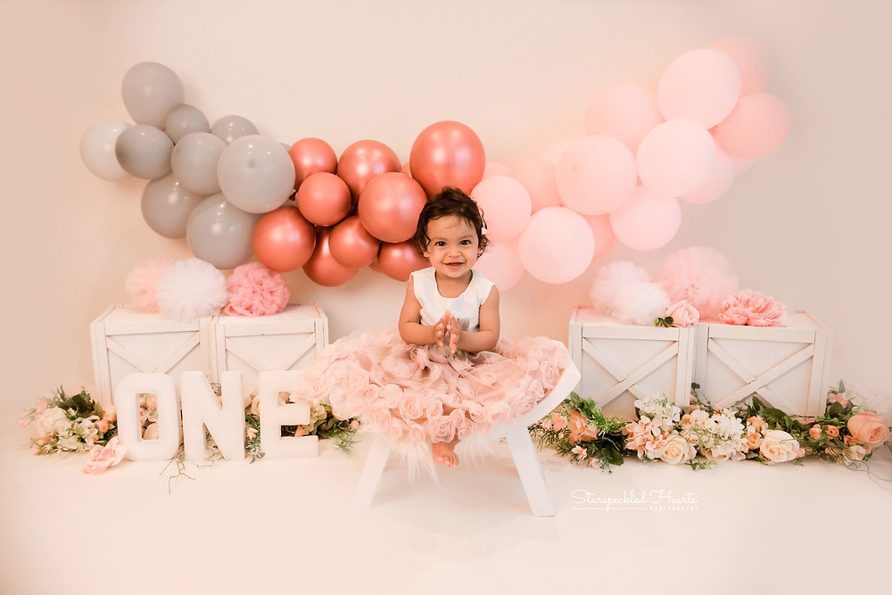 A smiling baby girl sitting on a curved stool wearing a pretty pink dress with a large balloon garland in the background for her first birthday cake smash and splash session in Aldershot, Hampshire