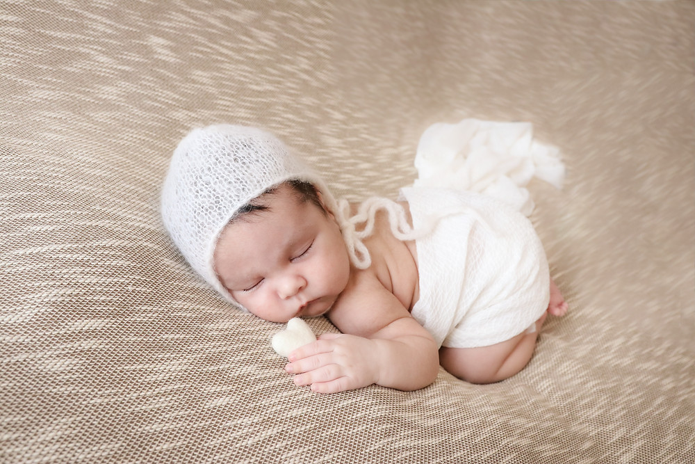 newborn boy lying on stomach wearing white bonnet holding white heart