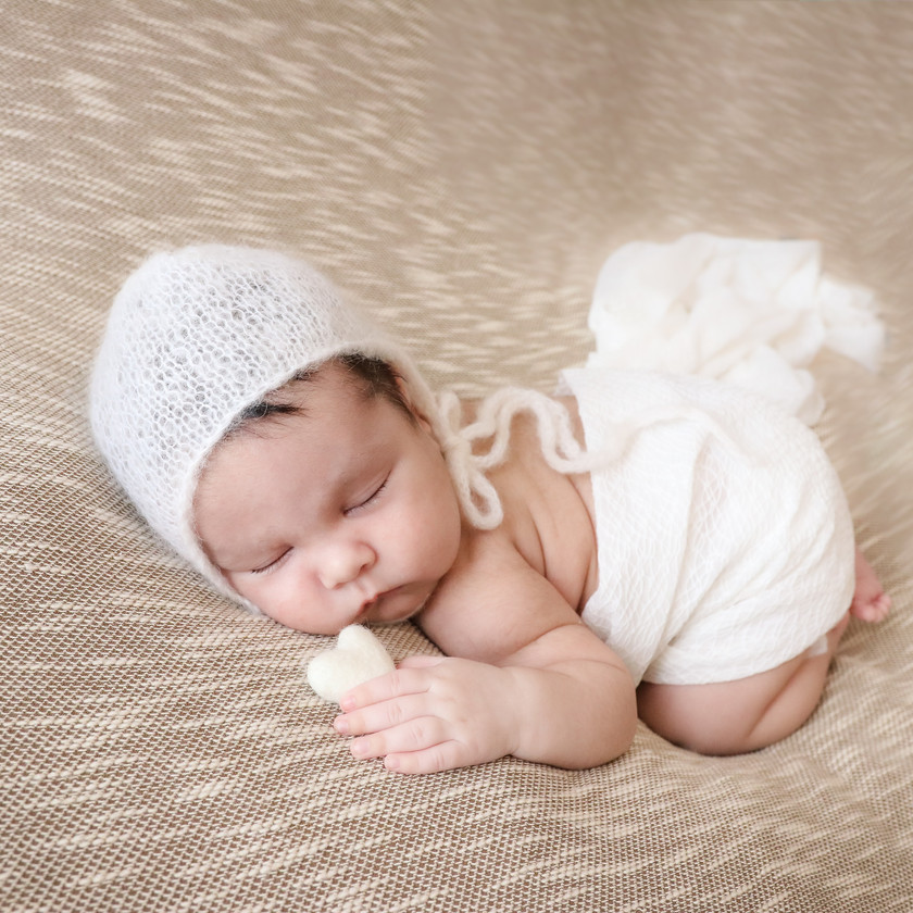 gorgeous sleeping baby boy wearing a white knitted bonnet and holding a white felted heart