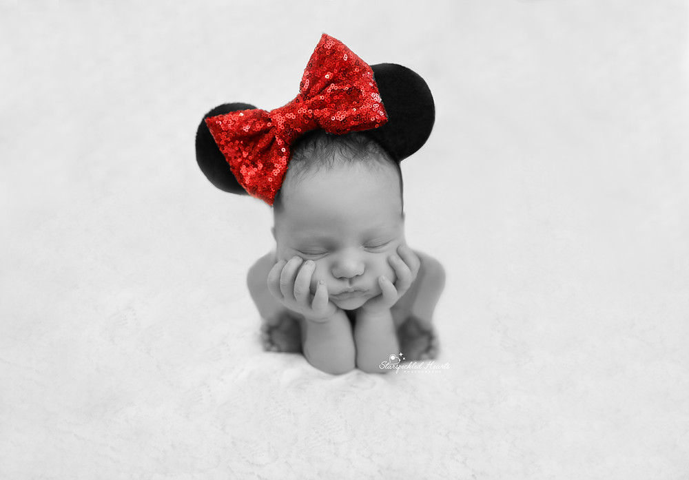 sleeping newborn girl in the froggy pose, wearing a minnie mouse headband with a big red bow
