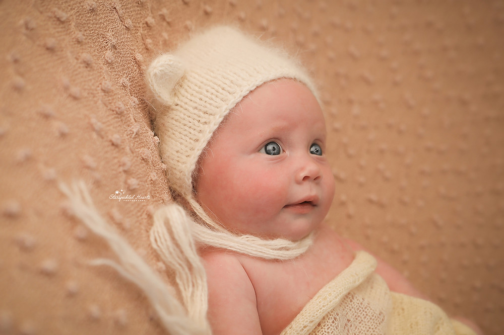 beautiful baby girl wearing a cream knitted bear bonnet lying on a pink blanket with big blue eyes