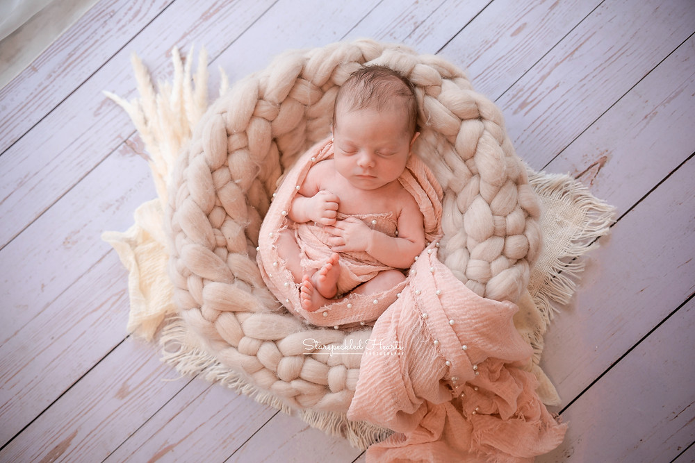 newborn girl swaddled with a pink pearl embellished wrap, lying in a cream woven basket for her newborn photoshoot in reading with starspeckled hearts photography