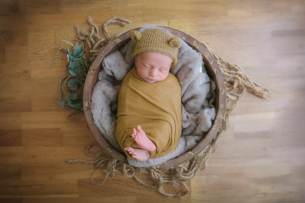 newborn baby boy wearing a mustard yellow bear bonnet and matching wrap, lying in a round wooden bowl