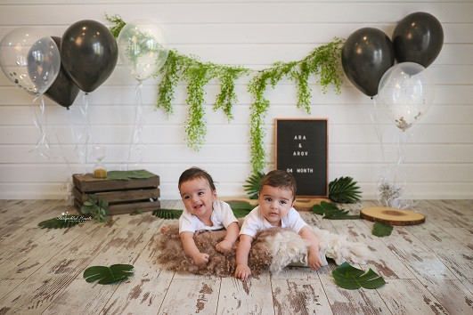 gorgeous twin boys lying on their tummies on a fluffy rug, with greenery, leaves and balloons behind them