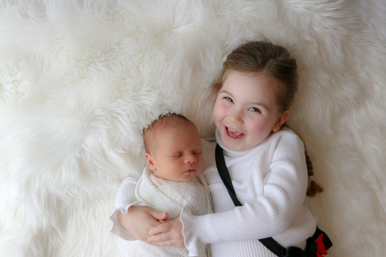 brown haired little girl lying next to her newborn baby brother cuddling him