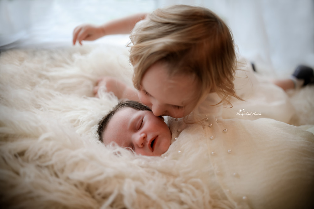 a swaddled newborn and her older sister lying down on a white rug together