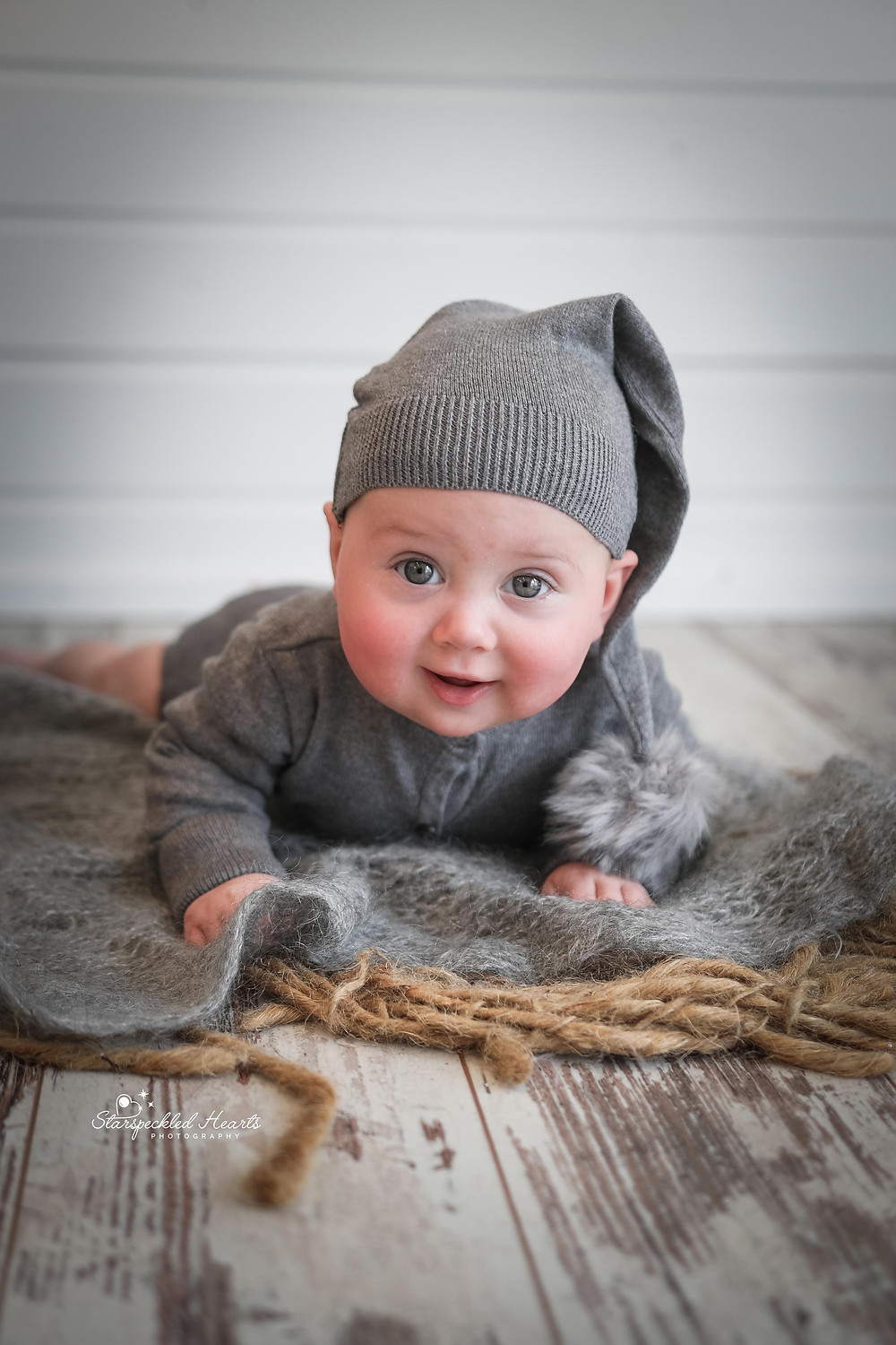 gorgeous smiling baby boy wearing a grey romper suit with a matching hat