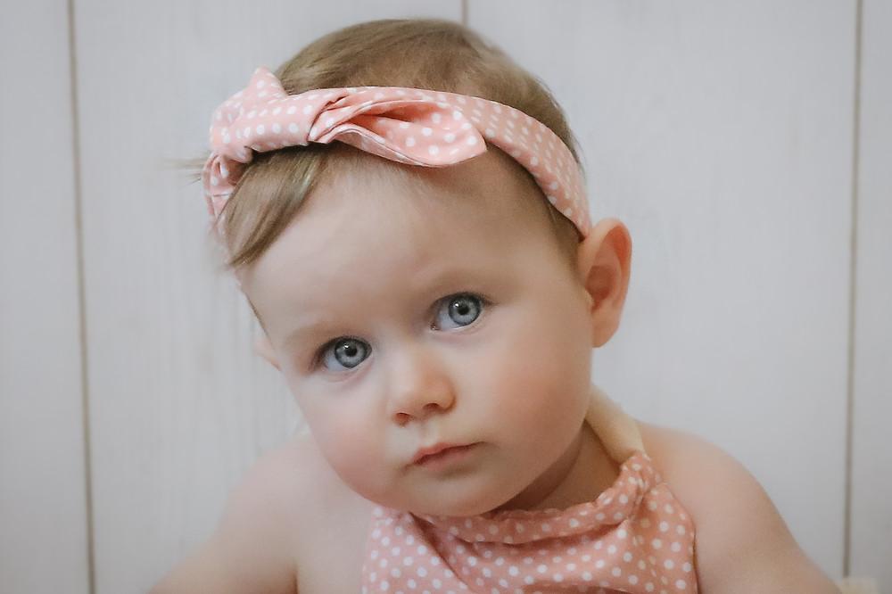 headshot of beautiful toddler girl with big blue eyes and pink headband