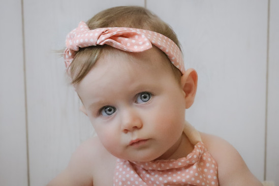 closeup of a gorgeous little girl with bright blue eyes and blonde hair, wearing a pale pink polkadotted hairband and matching romper suit