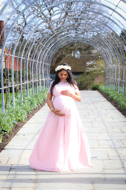 beautiful pregnant woman with long black hair wearing pink flowy dress, standing underneath a large metal arch in rhs wisley botanical gardens