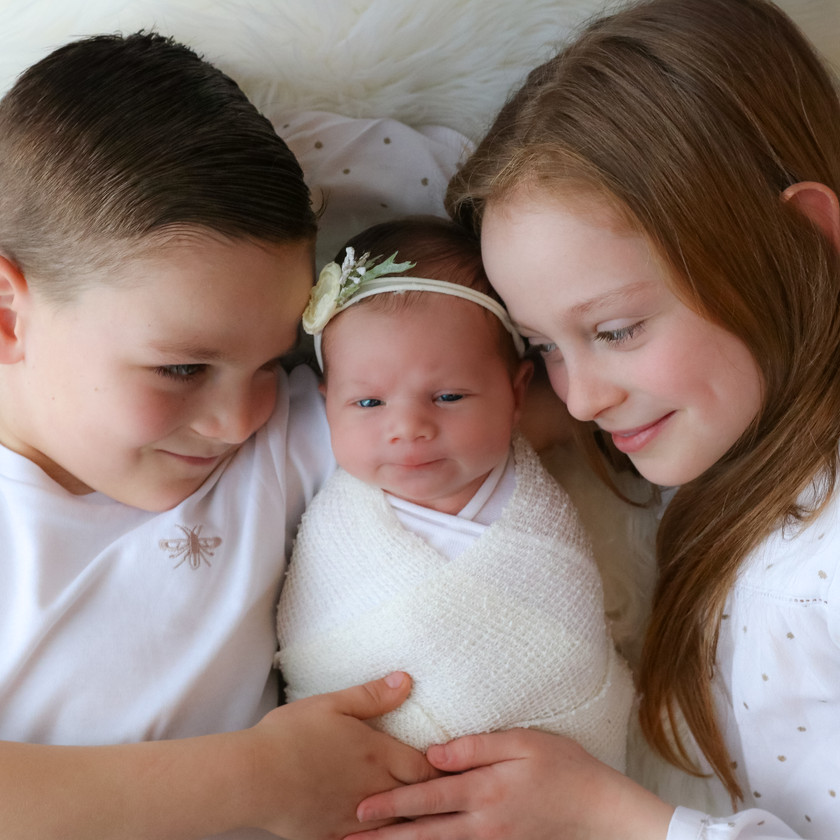 two older siblings with arms around each other and hands on newborn