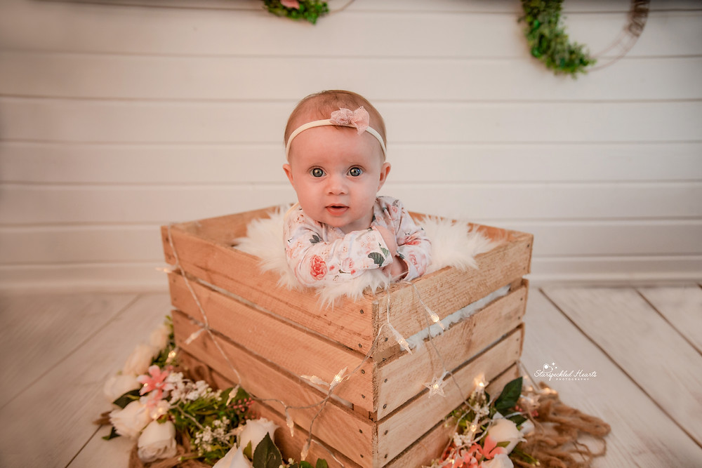 cute baby girl lying in a crate surrounded by flowers