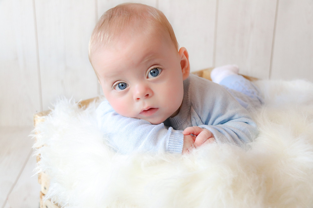 gorgeous baby boy with the biggest blue eyes, wearing a blue sleepsuit, lying in a crate stuffed with a white fluffy rug