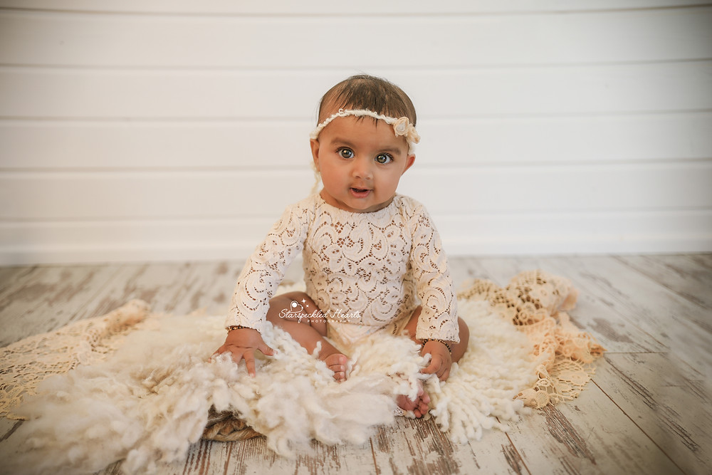 beautiful baby girl wearing a white lacy romper, sitting on a white rug