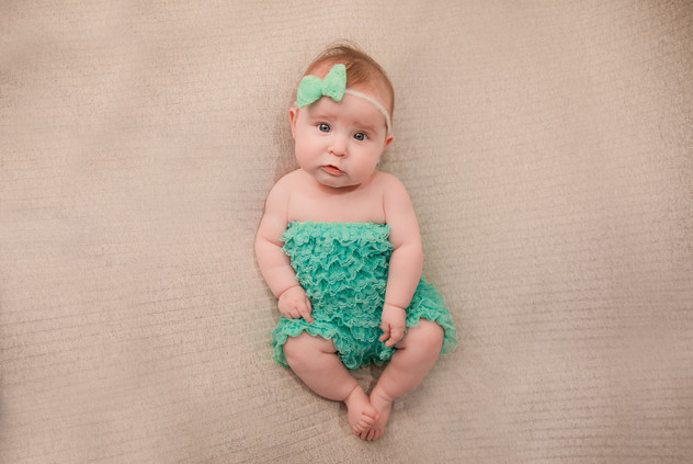adorable baby girl wearing  a turquoise frilly romper and matching headband
