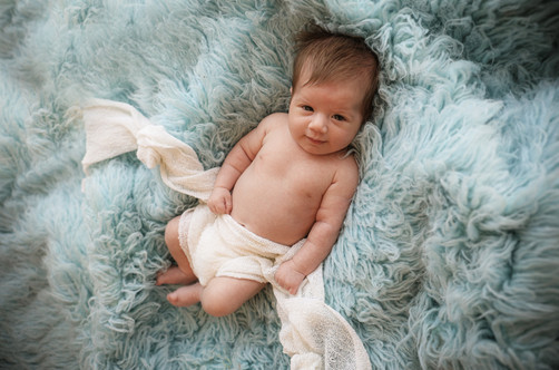 newborn lying on a blue furry rug for his newborn photography session with starspeckled hearts