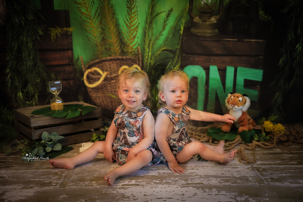 twin boys wearing matching jungle book rompers