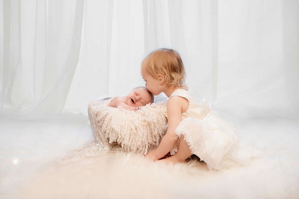 sibling photography as part of a newborn session, an all white setup with big sister giving her smiling baby sister a kiss on her head at her newborn photoshoot in hampshire