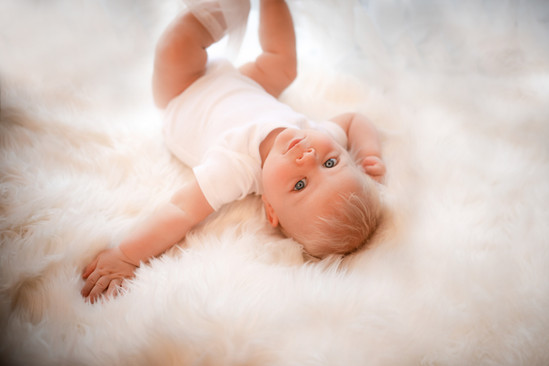 blonde baby boy lying on his back on a white fluffy rug, looking up at the camera