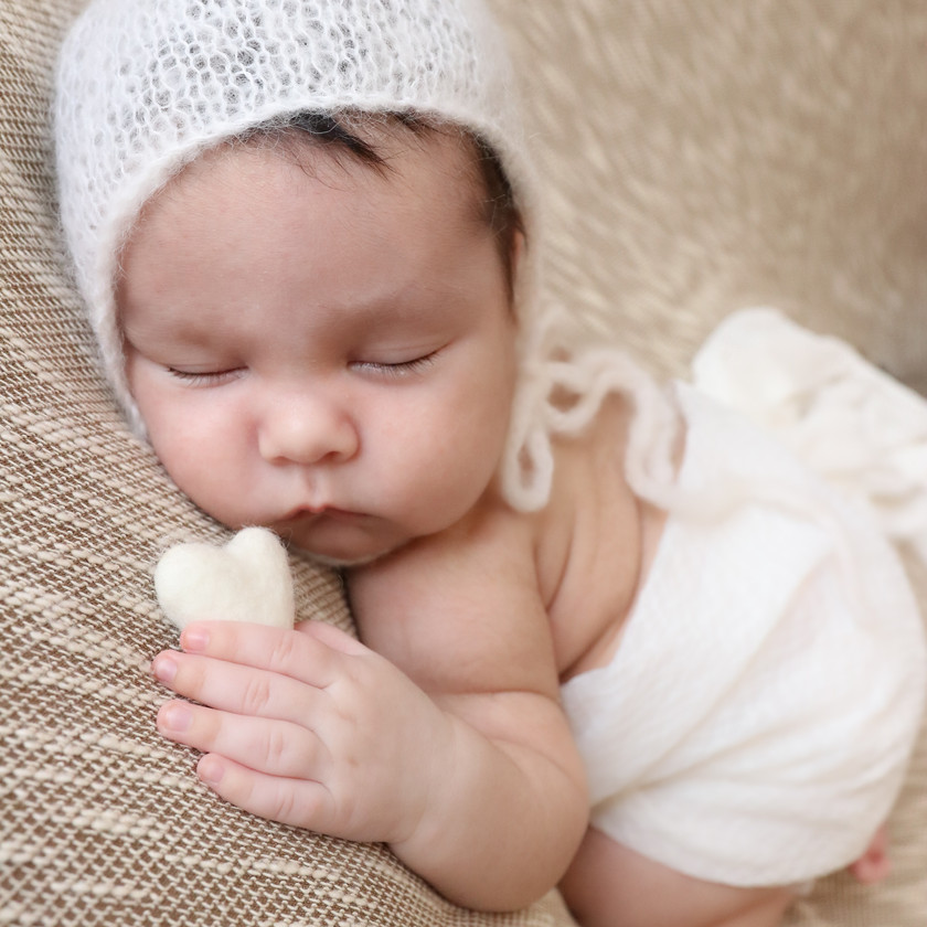 gorgeous sleeping baby boy wearing a white knitted bonnet and wrap, holding a felted heart in his hand