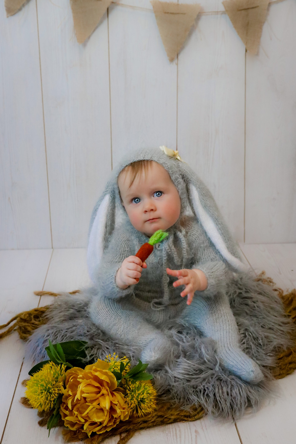 toddler girl sitting on grey furry rug wearing grey bunny outfit with bunny ears