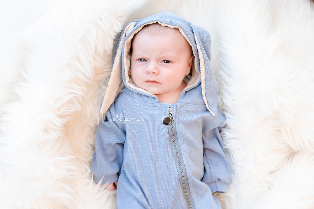 newborn wearing a blue romper with bunny ears, lying on a white fluffy rug for his newborn photography session with starspeckled hearts photography