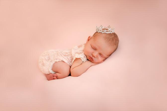 adorable baby girl lying on a pink blanket