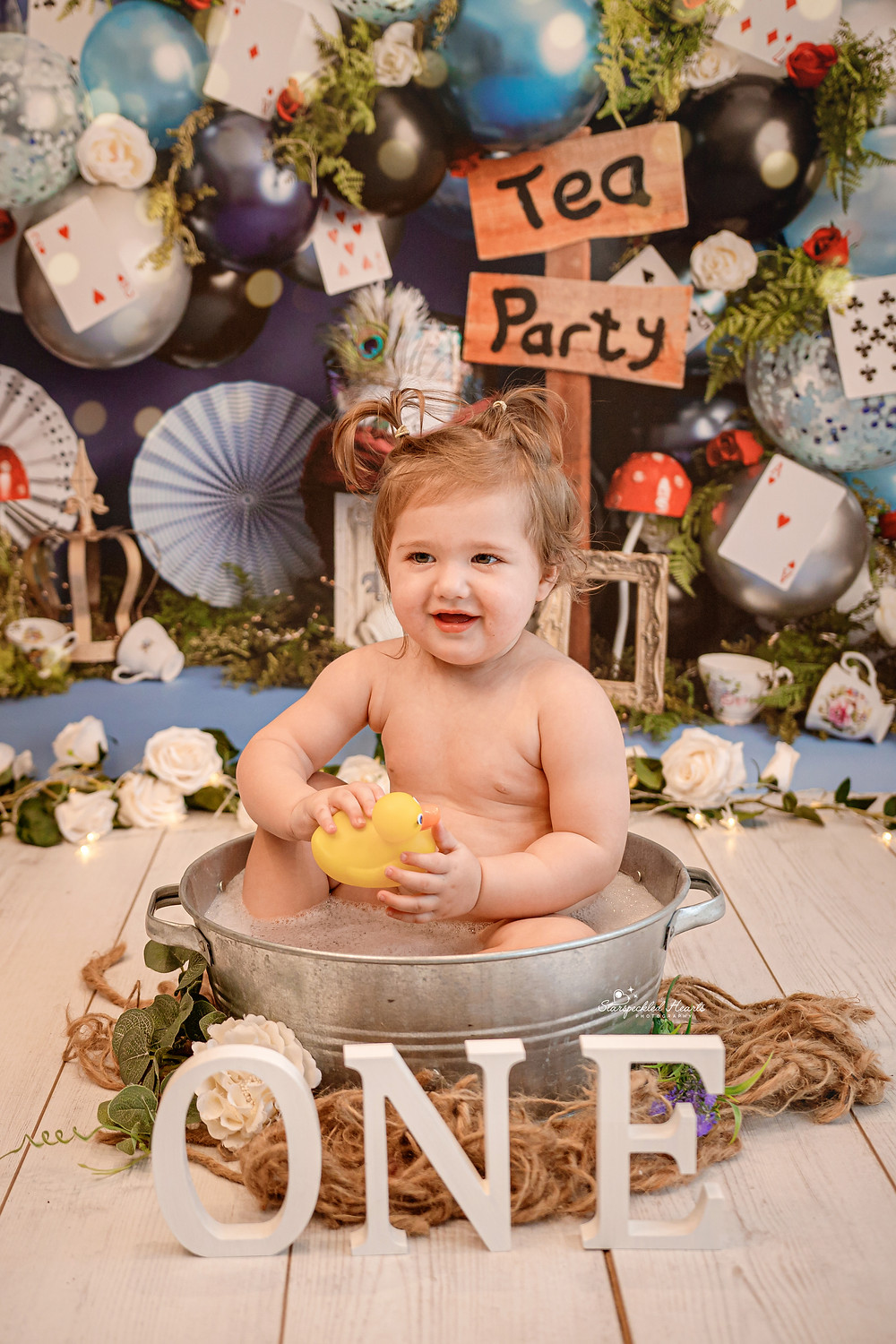 smiling baby girl sitting in a metal washtub with the letters one in front of her