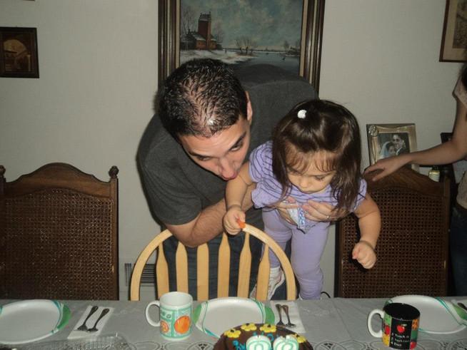Tom blowing out the candles on his birthday with the help of our niece.  Tom soplando las velas con la ayuda de nuestra sobrina.