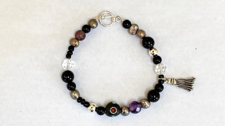 Black and purple beaded bracelet with tassel