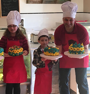 A family holds green and yellow cakes.